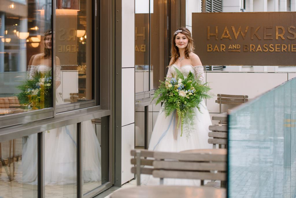 bride holding wedding bouquet outside wedding venue