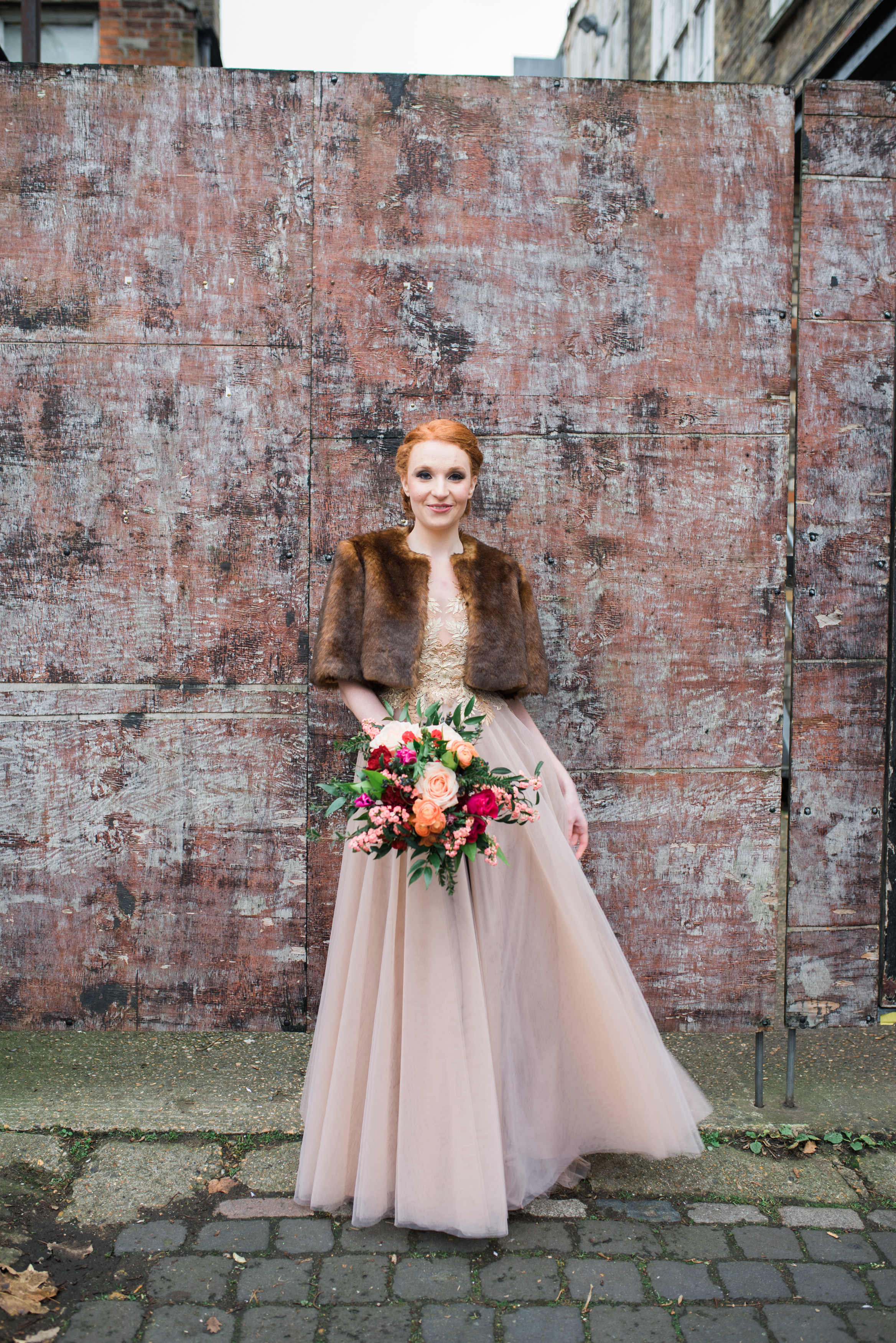 bride outdoors in rose gold tulle wedding dress with faux mini fur coat