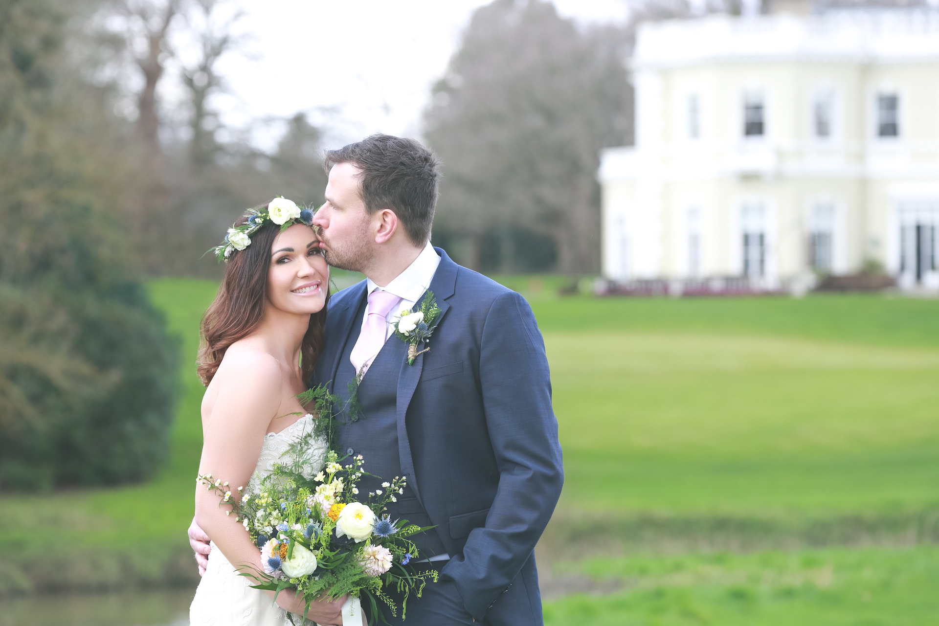 groom kissing bride on forehead on the grounds of burhill golf club