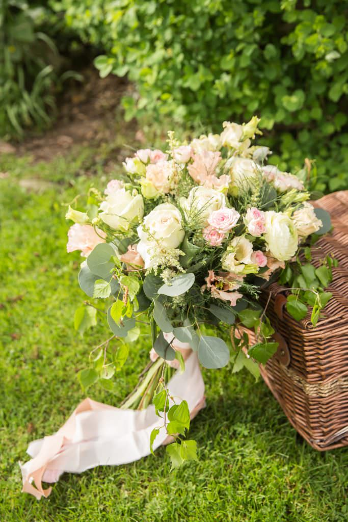 bouquet against picnic basket with silk ribbons