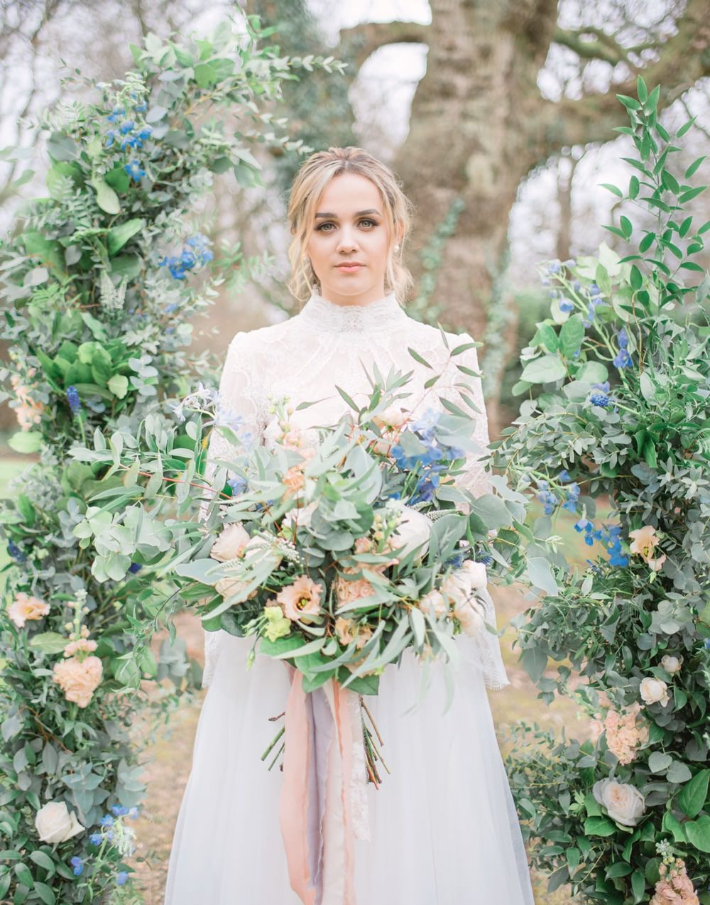 bride holding oversized wedding bouquet in front of deconstructed floral arch for wedding ceremony
