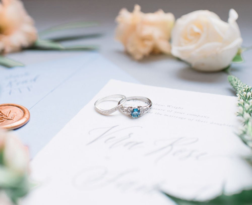diamond wedding rings and wedding invitations used to postpone a wedding