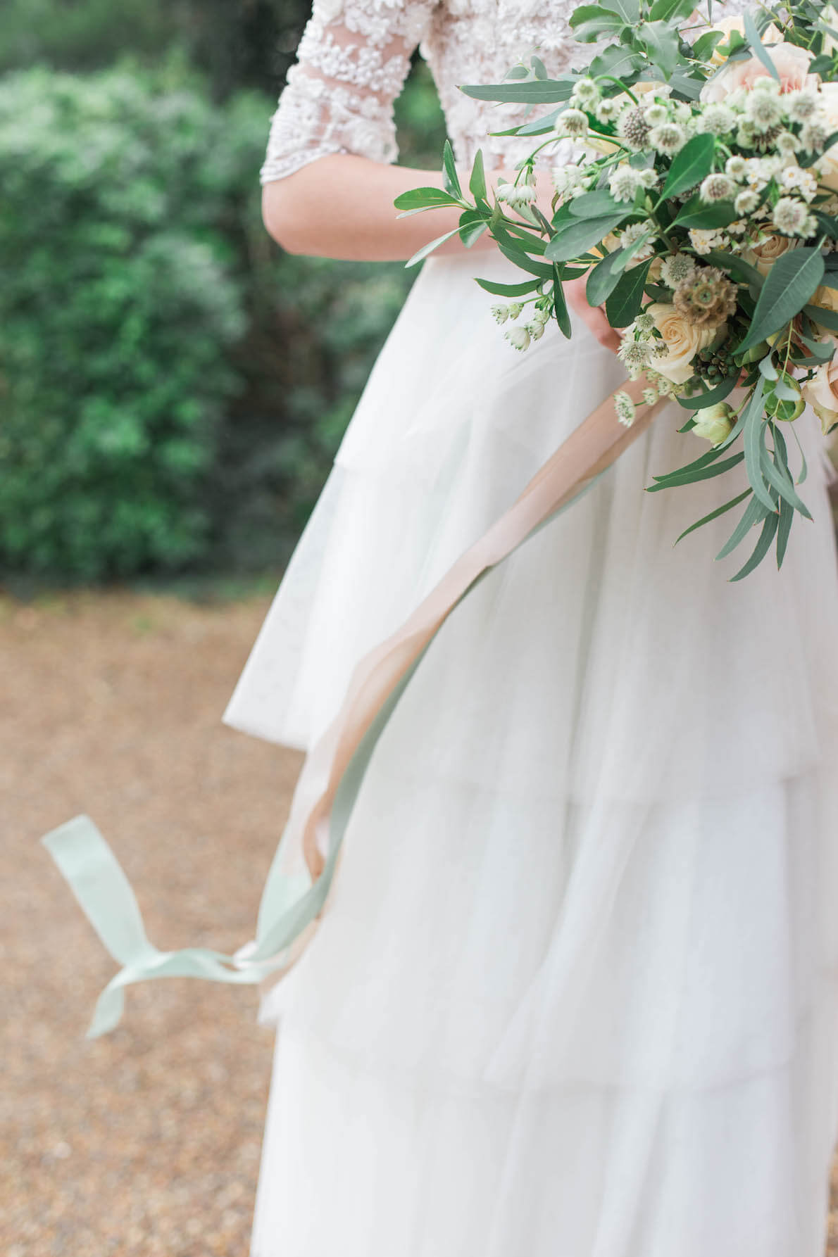 part of bride holding bouquet