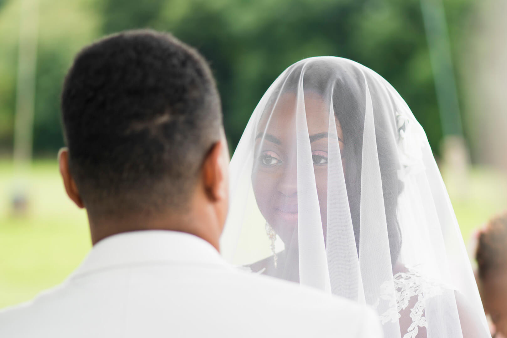 bride wearing a veil about to exchange vows with groom