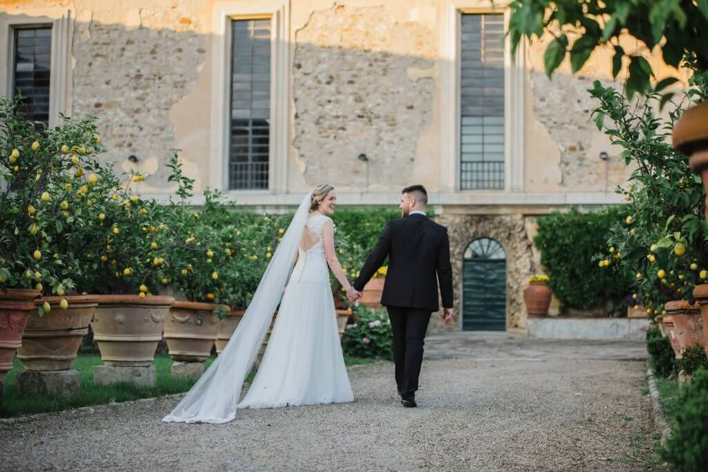 couple holding hands on wedding day on the grounds of villa pazzi